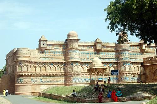 Unter einem Baum sitzen Inder vor dem Fort; zu sehen sind die Details im Mauerwerk