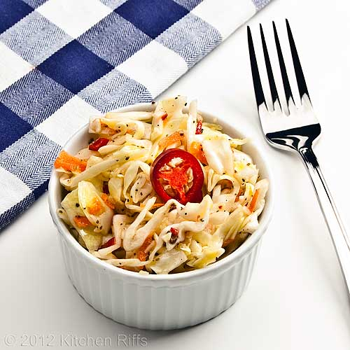 Garlic Coleslaw with Red Jalapeño Pepper Garnish in White Ramekin on White Background