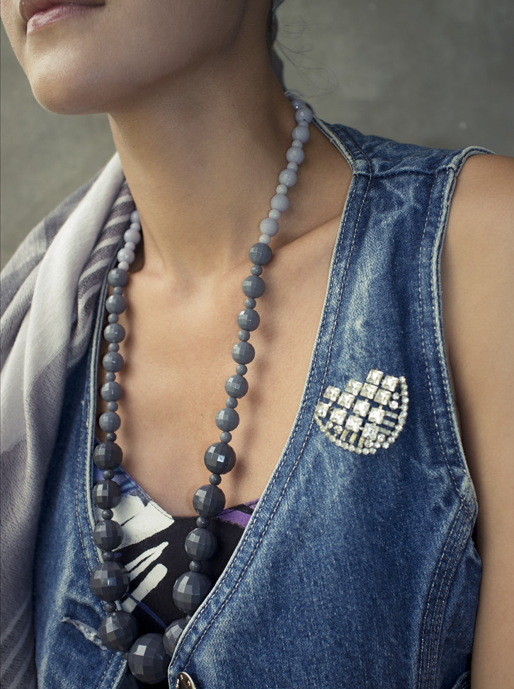 Mix up your accessories! In this photo, a graduated grey beaded 1980s necklace sits next to a 1940s rhinestone brooch.