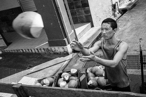 A chinese worker unloading coconuts from a lorry. Little India, Singapore