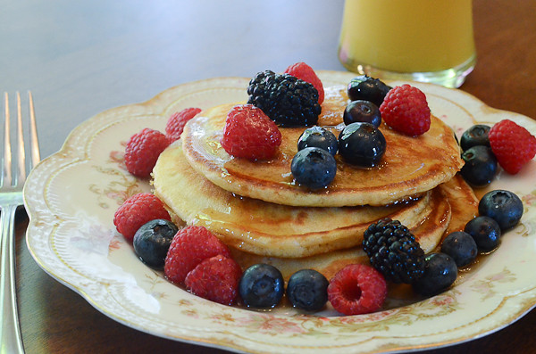 Mom's Buttermilk Pancakes covered in syrup and berries.