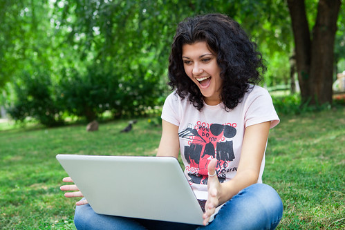 Girl Using Laptop in park | by CollegeDegrees360