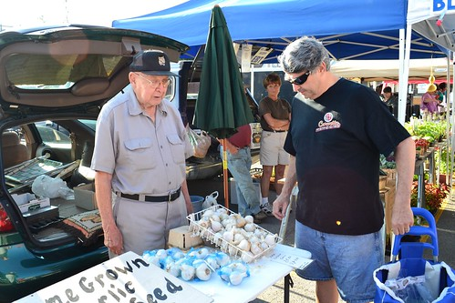 Elmer Moje sells German Stiffneck garlic at his stand in the Tonawanda, New York farmers market.  For decades, Moje has been bringing his crops to the same market.  Photo by Sharif Hamdy