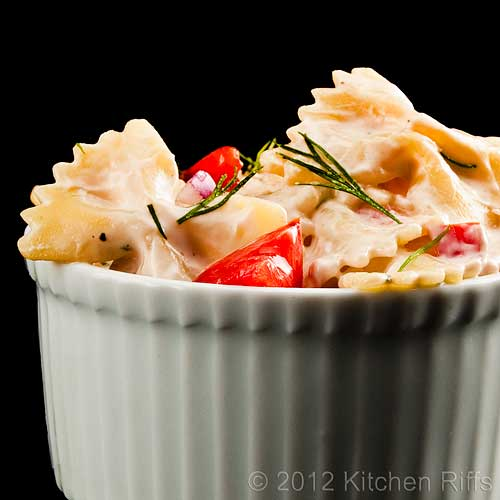 Pasta Salad with Dill Garnish in White Ramekin, Black Background