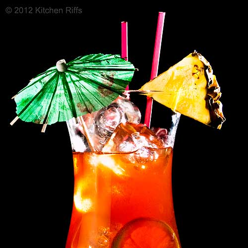 Planter's Punch Cocktail with Pineapple Garnish and Umbrella, Black Background
