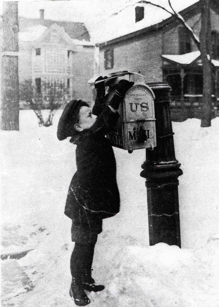 Boy putting letter in mail box