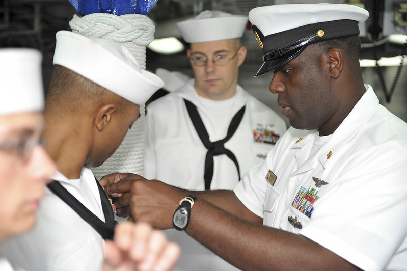 Chief Aerographer's Mate Fredrick Baker (right) adjusts ribbons on Aerogapher's Mate 3rd Class Bryan Owens