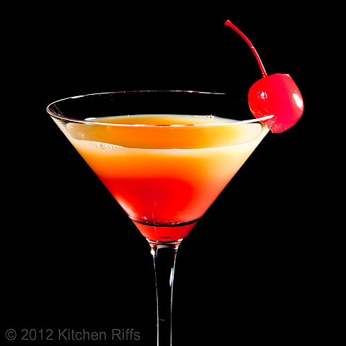 Tequila Sunrise in Cocktail Glass with Cherry Garnish, Black Background