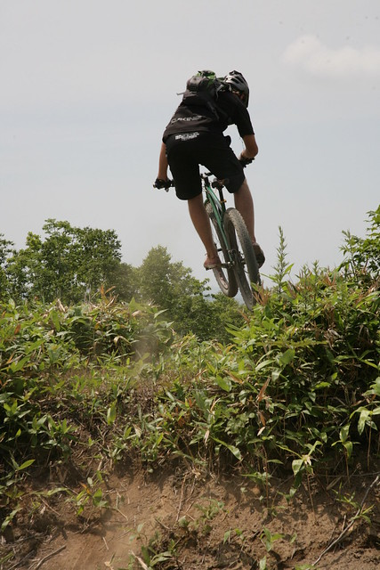 Rear view of a cyclist riding a green Surly Krampus bike over a small, grassy hilltop