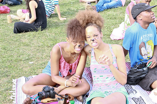 fans sitting on a blanket at the festival wearing facepaint