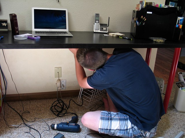 Aaron installing the cord basket under the desk.