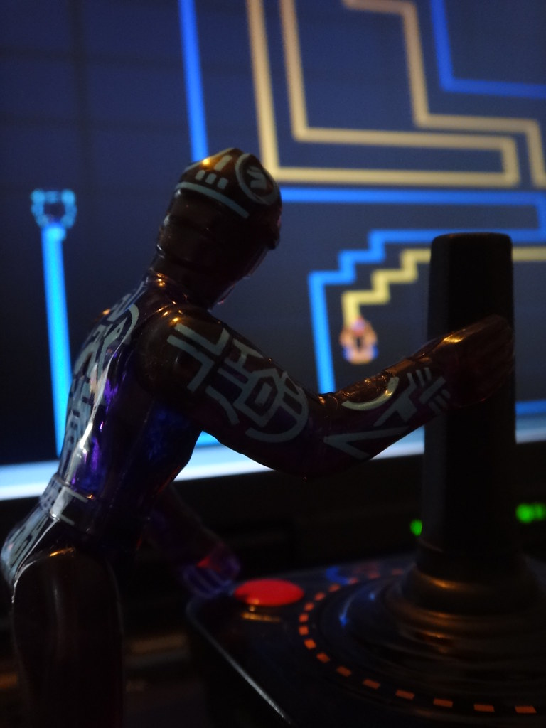 Tron action figure playing lightcycle video game with Atari joystick