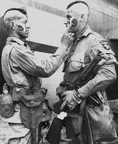 "This photo of paratroopers Clarence C. Ware and Charles R. Plaudo painting each other's faces on the afternoon of June 5, 1944, was printed in Stars and Stripes, and helped form the legend of ""The Filthy Thirteen."""