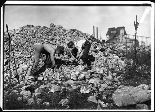 Two young boys collecting rocks, 1912