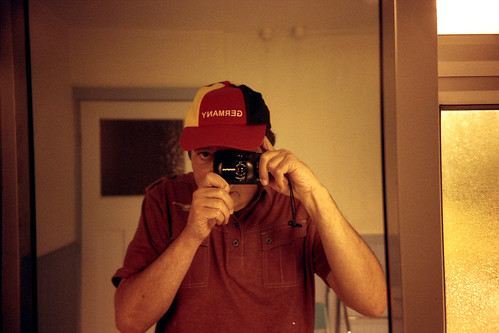 reflected self-portrait with Olympus XA4 camera and Germany cap by pho-Tony
