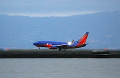 Boeing 737 Southwest Canyon Blue colors, landing at SFO, wing strobe lit.