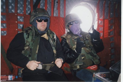 Musician composer Billy Hale with band member, being deployed to play music for the troops, sponsored by the United States Department of Defence (DOD), in a troop carrier high above a war zone, in safety belts, helmets, jackets, with their amps by Wonderlane