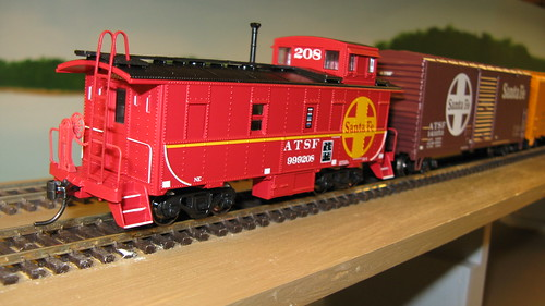 Santa Fe freight train passes with a red caboose on the rear. by Eddie from Chicago