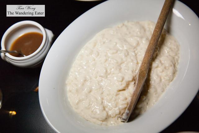 Large serving of rice pudding and a pot of caramel sauce