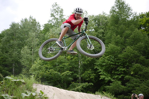 Right side view of a cyclist, on a green Surly Krampus bike, launching off of a dirt ramp with trees in the background