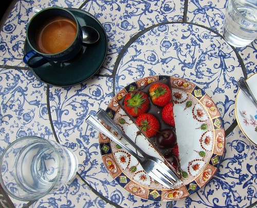 Top-down view of a café table with a cup of espresso and a piece of rich, dark chocolate tart covered with strawberries and cherries.