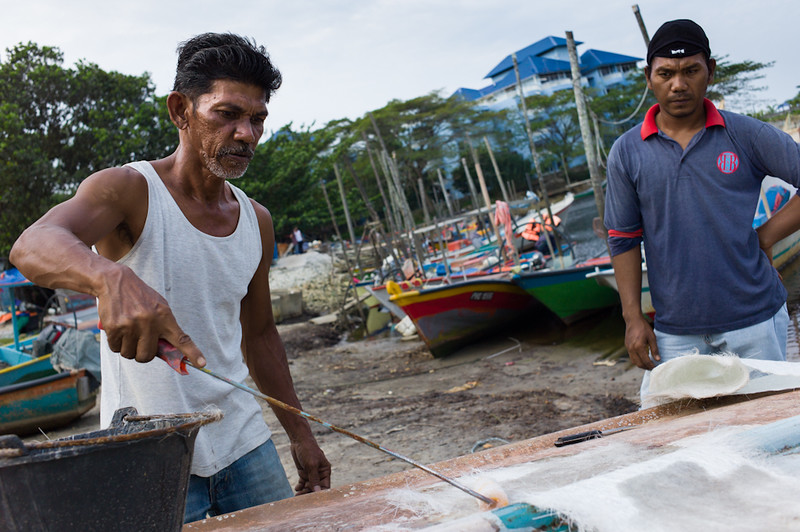 Workers repairing fishing boats in Trengganu, Malaysia.