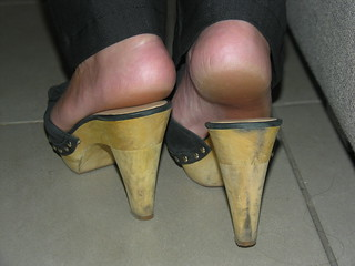 Backview of young MILF wearing wooden slides, exposing her sexy hot and smelly soles