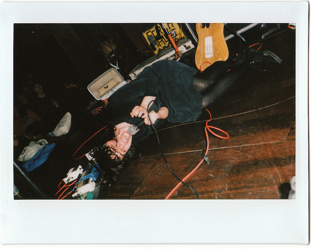 marissa paternoster from screaming females on the floor of a wooden stage with her microphone screaming into it
