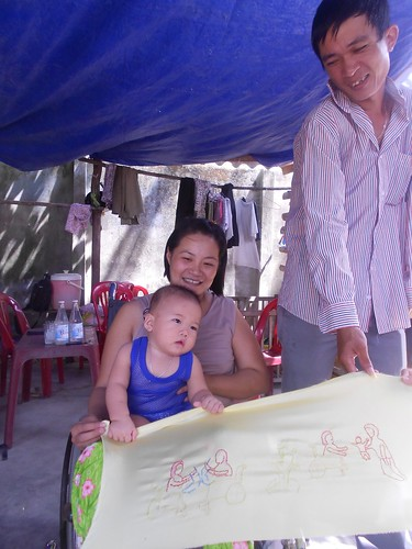 Ms. Long Ngru with her quilt and family