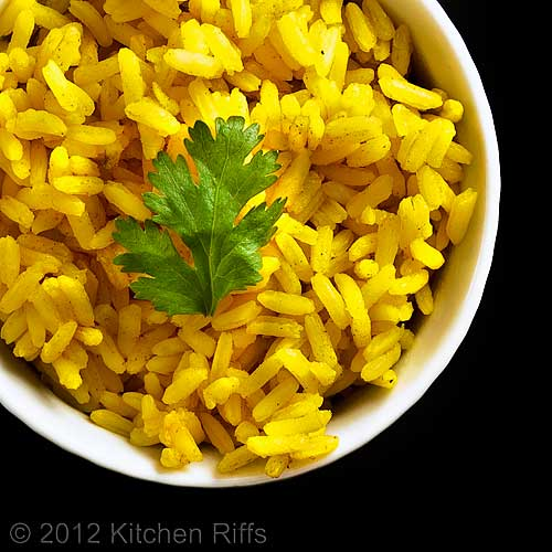 Aromatic Indian Yellow Rice with Cilantro Garnish in White Ramekin, Overhead View with Black Background