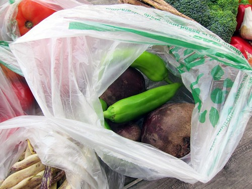 Plastic bag with long green peppers and large, dark purple beets.