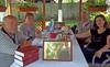 Enrique Schaljo mit Ehefrau aus Argentinien und die Csontis in der Sommerlaube im Heimathaus. Im Vordergrund eine von ihnen mitgebrachte Gedenktafel für das Heimatmuseum mit den Nachkommen von Heinrich Schaljo die heute in Argentinien leben.