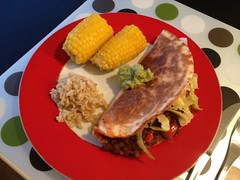 Enchiladas with black bean chili, guacamole, rice & corn cob