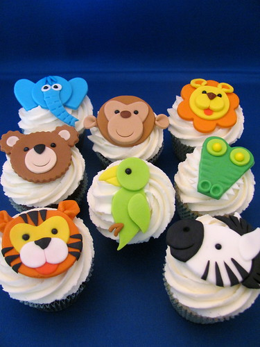 The ones on the bottom are Dinosaur Train cupcakes. Contact them at  zoeycakes at gmail.com and visit zoeycakes.com for more information.