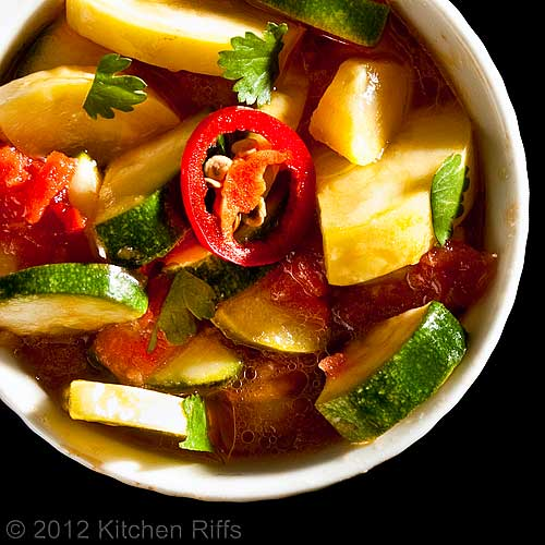 Summer Squash in Tomato Curry Sauce in White Ramekin on Black Background, Overhead View