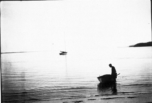 Man with a dinghy in the shallows