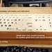 <p>DIY keyboard support for supine surfing. Foundation is an inexpensive, lightweight cork board, used cork side down. A piece of fir door casing molding is cut to fit and glued to the fiberboard back of the cork board. The molding has a wedge profile. The wider part of the wedge keeps the keyboard from slipping down the board and provides a smooth surface for the heel of the hand when keyboarding. Molding is sanded and finished with a natural oil and beeswax finish. <br /> <br /> The keyboard is a standard Apple wired keyboard. The keyboard cover is washable silicone with big, readable letters. It keeps schmutz out of the keyboard.</p>