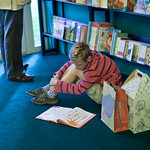 Young reader in the bookshop | A young reader engrossed in a book in the RBS Children's Bookshop