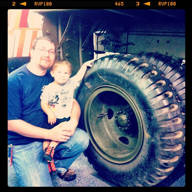 Dad and boy next to the tire of a WW2 tow truck used on the beaches of Normandy.