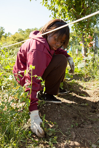 A student tends the garden at Baldwin center