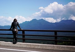 Japanese biker girl in leathers looking at mountains (Mikuni Pass, Hokkaido, Japan)