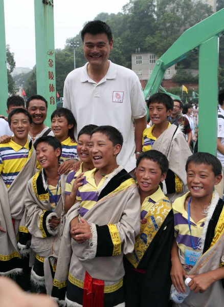 August 24th, 2012 - Yao Ming poses with children at a basketball camp in Sichuan