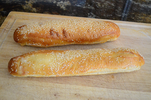 Two baguettes on a cutting board.