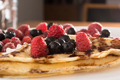 Fresh, golden pancakes with fruit and cream