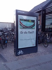 "This is a public air pump for bikes.  The sign reads, ""Are you flat?  Use the bicycle pump right here."""