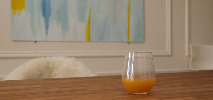 butcher block table, aqua painting, yellow accents, masonite painting, glass of peach juice