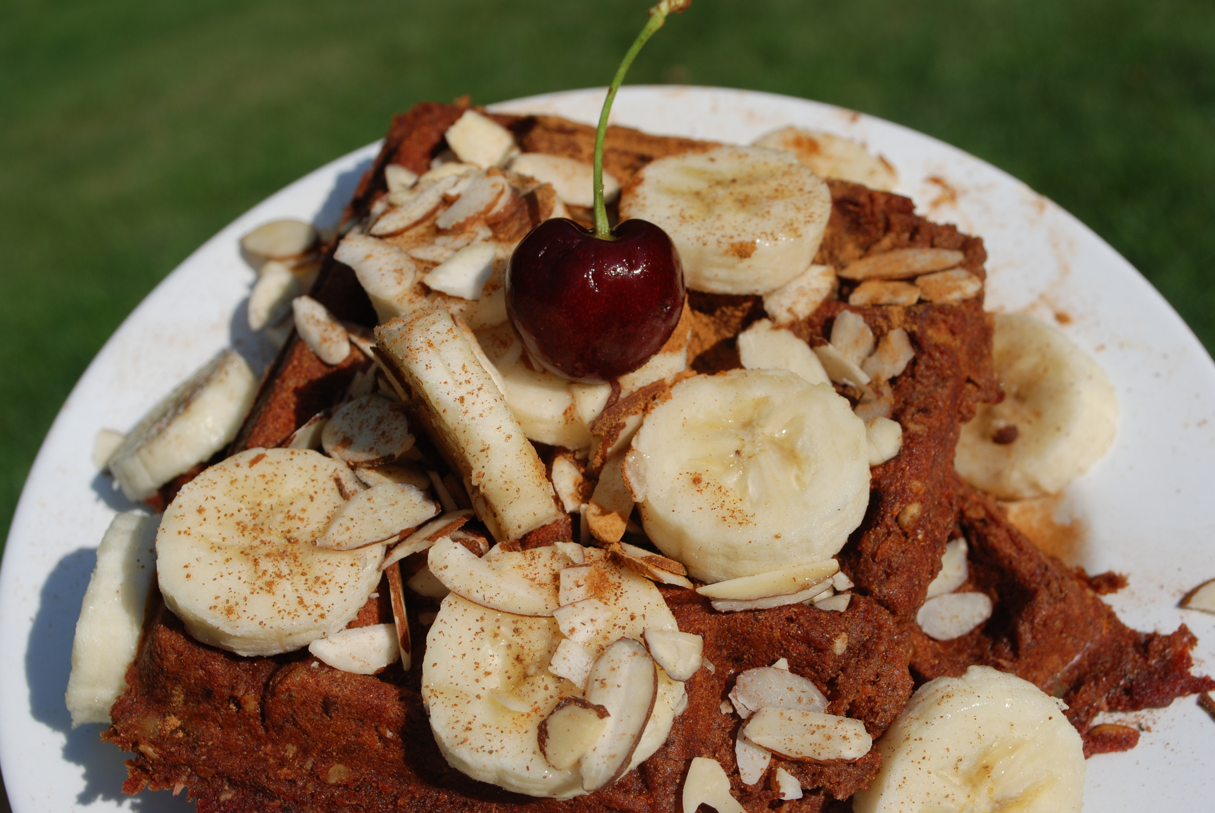 Nutrient-Dense waffles topped with sliced bananas, shredded almonds, cinnamon, and a cherry on top!