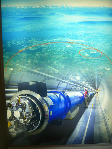 Poster na recepção, mostPoster na recepção, mostrando o anel seccionado do LHC e o túnel, além de um mapa demostrando a extensão do LHC, com os Alpes ao fundo.