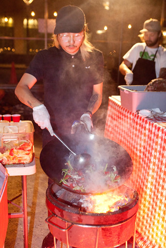 Chef/Owner Danny Bowien of Mission Chinese stir frying with his wok on a portable gas grill