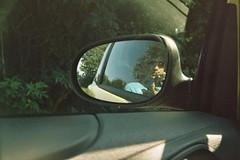 driving(0.0), wheel(0.0), bumper(0.0), windshield(0.0), automobile(1.0), glasses(1.0), automotive exterior(1.0), automotive mirror(1.0), vision care(1.0), window(1.0), vehicle(1.0), rear-view mirror(1.0), light(1.0), glass(1.0), green(1.0), sunglasses(1.0),